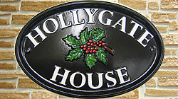 The holly, with its bright red berries, and the white lettering conjures up beautiful snowy winter scenes, but this bright cheerful sign is welcoming whatever time of year. The lettering is set out in Times on the top and bottom curves