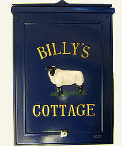 The gold Times Condensed lettering, set out in a curve above the sheep and in a straight line below, looks elegant on the blue background of this large personalised post box