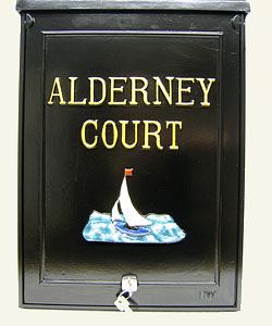 This sample of a large personalised post box shows gold Times Condensed lettering set out in two straight lines above the emblem of the yacht